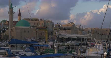 akko : ACRE, ISRAEL- MARCH 12, 2017: Evening scene of port with boats at anchor and view to old city with Sea Mosque Stock Footage