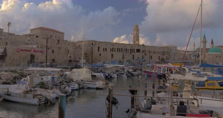 akko : ACRE, ISRAEL- MARCH 12, 2017: Panning shot of the port with boats at anchor. Scene with Khan al-Umdan and Sea Mosque Stock Footage