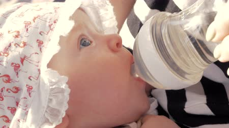gözlü : Close-up shot of a blue-eyed baby girl in bonnet drinking water from plastic bottle outdoor Stok Video