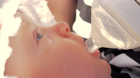 szomjúság : Close-up shot of three months baby in bonnet drinking water from the bottle outdoor on summer day