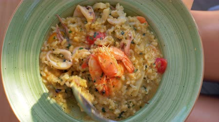 kalmar : Close-up shot of eating sea food risotto with squid and prawns. Dining in outdoor restaurant
