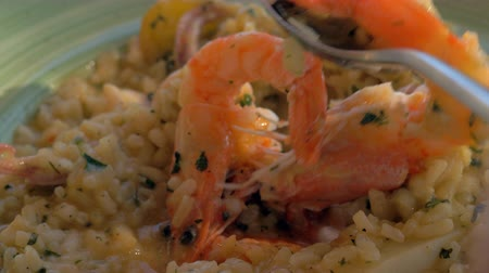 основное блюдо : Close-up shot of eating risotto with prawns and squid. Dining in sea food restaurant