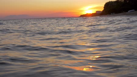 scenes : Slow motion shot of dark sea waves rolling in the shore. Beautiful waterscape at sunset