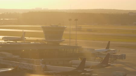 parkoló : Airport view with jets, terminal and control tower at sunset. Airplane taking off from runway