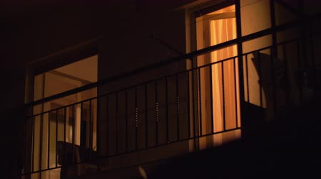 тусклый : Night view of the house balcony with open doors and dim light inside