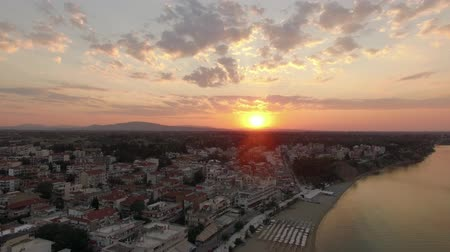 chaise longue : Aerial shot of small town with many low rise houses at sunrise. Copter flying away and opening panorama with coastline and sea. Nea Kallikratia, Greece