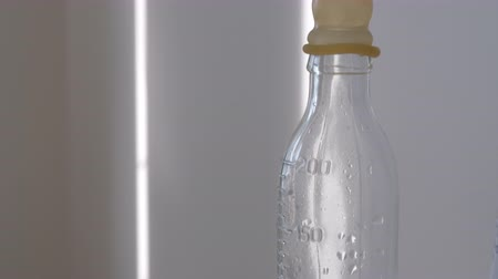 nipple : Close-up shot of water in glass bottle with teat in maternity hospital Stock Footage