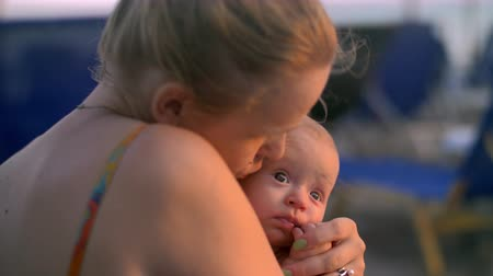 outing : Slow motion shot of a mother hugging and kissing cute beloved baby daughter. Family outing at the beach Stock Footage