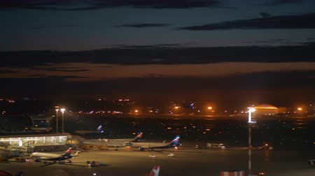 takeoff area : MOSCOW, RUSSIA - AUGUST 07, 2017: Illuminated Sheremetyevo Airport at night. View to the terminal with control tower, parked jets and airplane taking off