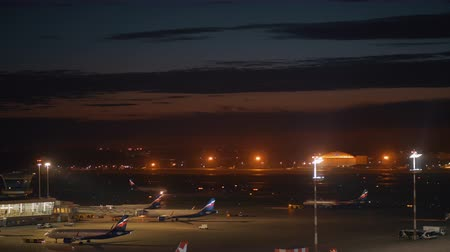 redazione : MOSCOW, RUSSIA - AUGUST 07, 2017: Sheremetyevo Airport at night. Tugs pushbacking two airplanes, while other airliners taking passengers on board