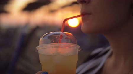buzlu : Slow motion close-up shot of a woman enjoying refreshing iced drink at the beach, sunset in background. Summer vacation
