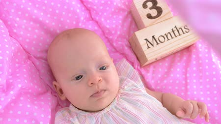 gözlü : Slow motion shot of a cute blue-eyed baby girl lying in pink bassinet with three months wooden sign