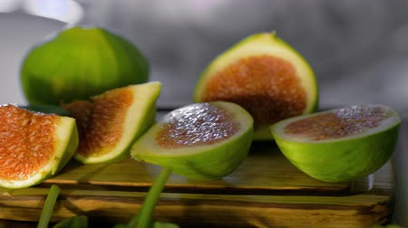 fig : Close-up shot of basil leaves falling on cut green figs on wooden board Stock Footage