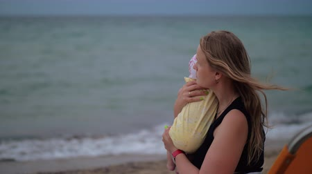 amado : Slow motion shot of a young mother hugging baby and staring at the sea sitting on chaise longue at the beach Stock Footage