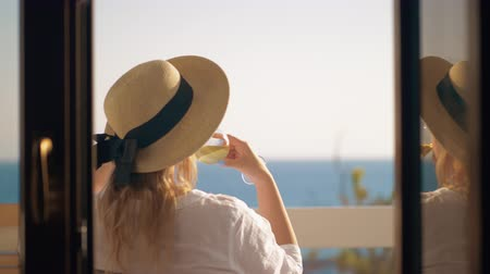 luksus : Back view of a woman in summer hat sitting at the balcony, drinking white wine and enjoying day looking at the sea