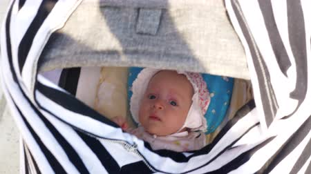 wozek dzieciecy : Mother pushing pram to lull the baby. Girl in bonnet looking from inside and isnt going to sleep to sleep Wideo