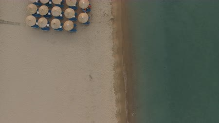 chaise longue : Aerial view of sea and beach with empty chaise-longues and straw umbrellas. Coastal resort