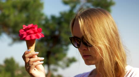 ワッフル : Close-up loop shot of a blonde in sunglasses spinning in hand waffle cone with red flowers and looking at it