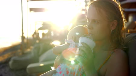chaise longue : Slow motion shot of mother with baby daughter relaxing at the beach during summer holidays. Woman refreshing with iced drink. View in bright sunset light