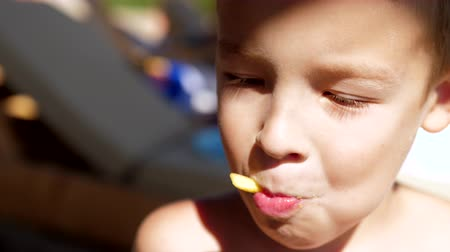 kalori : Close-up shot of boy eating French fries at the beach. Child having fast food snack at the seaside Stok Video