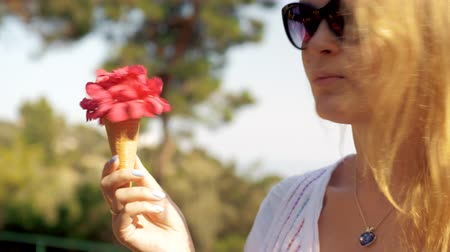 coquettish : Loop shot of coquettish blond girl in sunglasses spinning in hand a red flower  bouquet  in waffle cone. Summer scene Stock Footage