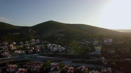 резиденция : Aerial shot of neighbourhood with cottages and flying up the green hills. View in bright sunlight. Trikorfo Beach, Greece