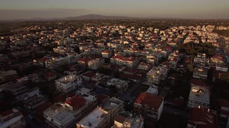 built up : Aerial view of densely built-up town. Flying over houses rooftops and streets in the light of morning sun. Nea Kallikratia, Greece
