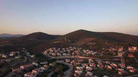 коттедж : Aerial shot of Trikorfo Beach cottages in the neighbourhood at the bottom of green hills, Greece