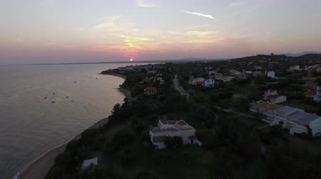 набережная : Aerial shot of sea and cottages along the shore, view at sunset. Trikorfo Beach, Greece Стоковые видеозаписи