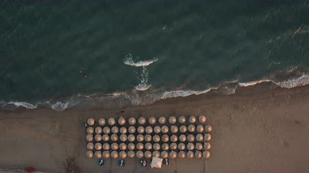 サンベッド : Aerial view of sea waves rolling in on the shore with rows of sunbeds under straw umbrellas. Coastal resort