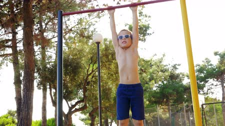endure : Slow motion shot of a kid in sunglasses hanging on chin-up bar at sports ground outdoor Stock Footage