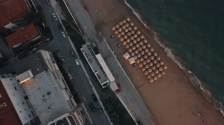 chaise longue : Aerial shot of town waterfront in the morning. Sea and beach with empty sunbeds, cars driving on the road. Nea Kallikratia, Greece Stock Footage