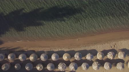 chaise longue : Aerial view of clear sea and beach with rows of straw sun umbrellas with sunbeds under them. Vacation on seaside resort Stock Footage
