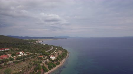 サンベッド : Aerial view of Trikorfo Beach coastline and sea, Greece. Green hills and houses on the shore. Recreational area with sunbeds at the seaside 動画素材