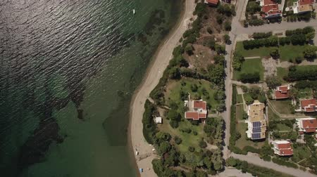napágy : Flying over the sea and coast with cottages and green yards alongside. Sunbeds at the seaside. Living on the shore. Trikorfo Beach, Greece Stock mozgókép
