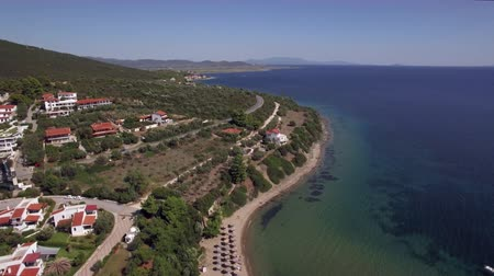 サンベッド : Aerial scene of sea and coastline of Trikorfo Beach, Greece. Cottages on the shore at the bottom of green hills, sunbeds at the seaside
