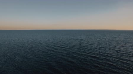 cisza : Flying over deep rippling sea at sunset. Vast blue water space and skyline