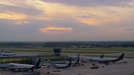 odejít : Evening view of the airport. Terminal with several planes boarding and one passenger jet taking off