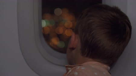 去る : Child having air travel at night. He looking out plane illuminator with view to illuminated city