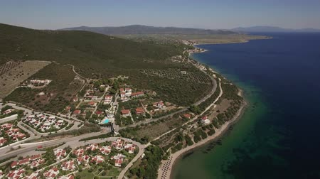 holiday villa : Flying over the town on the coast at the bottom of green hills. Scene with sea and Trikorfo Beach shoreline, Greece