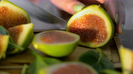 fig : Close-up shot of woman cutting green fig in half on the wooden board with basil leaves Stock Footage