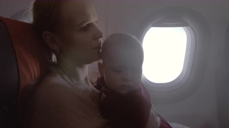 air kiss : Mother with baby in plane. Woman hugging child and kissing her. Family air travel