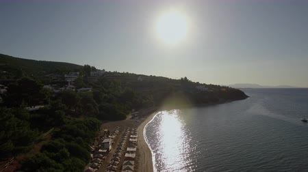 grecja : Flying over the sea and coast with sunbeds. View to resort at the seaside in bright sunshine, lights reflecting in water and sparkling. Trikorfo Beach, Greece