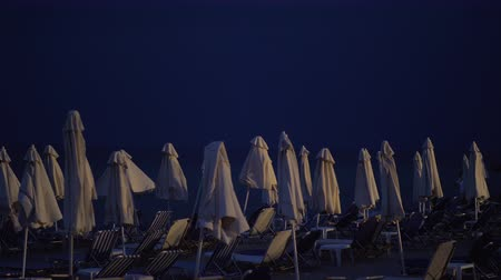 descarga : Slow motion shot of wind waving folded umbrellas at the beach with empty sunbeds. Night thunderstorm is coming and lightning striking over the sea