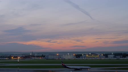 takeoff area : MOSCOW, RUSSIA - SEPTEMBER 11, 2017: Two airplanes driving on the area of Sheremetyevo Airport in the dusk. View with hangars