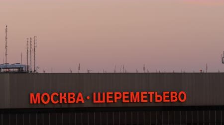 chegada : MOSCOW, RUSSIA - AUGUST 07, 2017: Evening sky and building of Terminal F at the airport. Illuminated red text with Moscow - Sheremetyevo Stock Footage