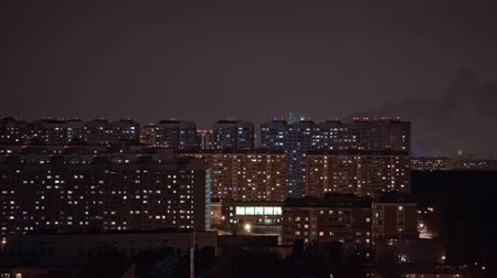 çok katlı : Timelapse shot of lights blinking in the windows of high-rise apartment blocks. Night city view with smoking pipes. Moscow, Russia
