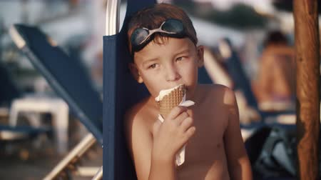 wistful : Slow motion shot of a boy enjoying vanilla ice-cream in waffle cone at the beach. He eating and looking at the sea being thoughtful and tired after active vacation day Stock Footage
