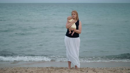 nyomasztó : Cinemagraph - Mother holding baby tight and looking frustrated. Shot against the sea, wind waving woman hair. Lone parent
