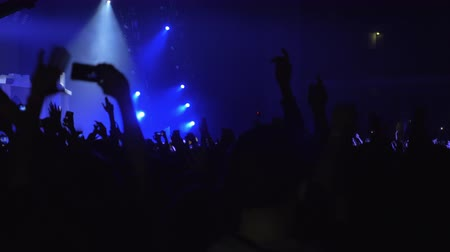 película de filme : Excited fans at the concert. Crowd of unidentified people dancing to music with hands up and shooting performance with mobiles. Bright blue stage lights in the darkness Stock Footage